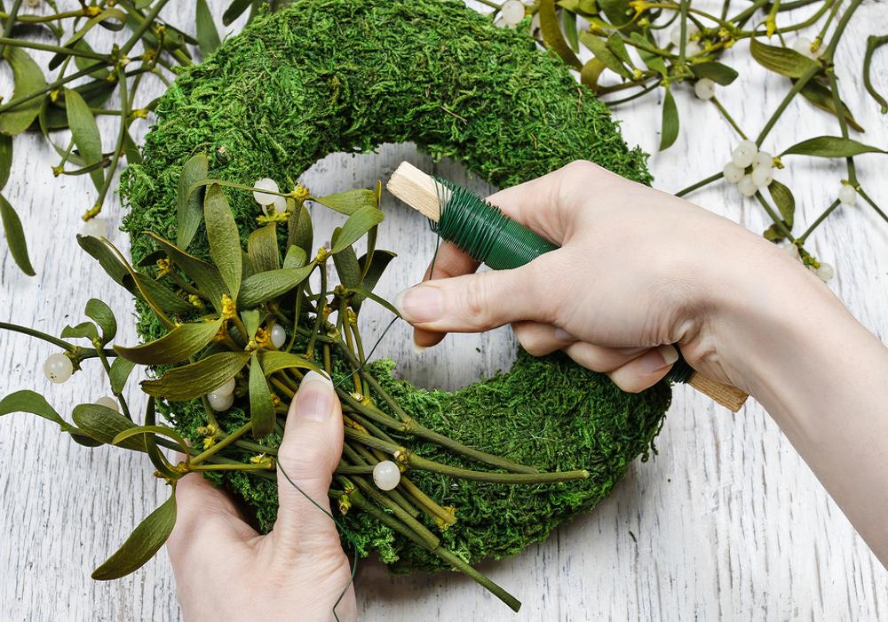 Ženské ruky tvoria zelený veniec na dvere