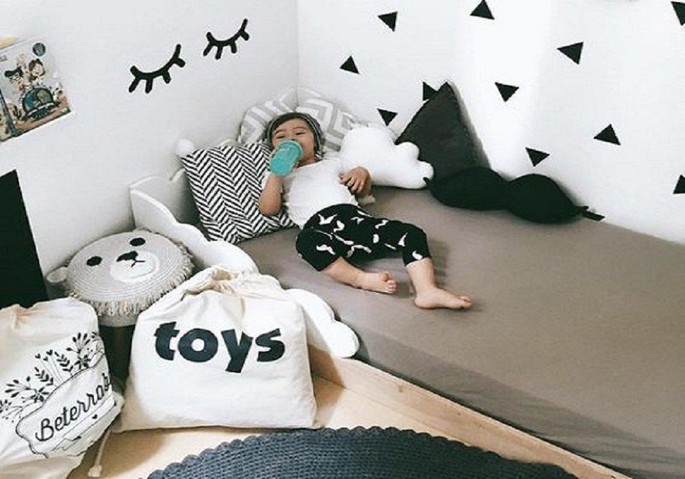 Dieťa ležiace na Montessori posteli pije mlieko