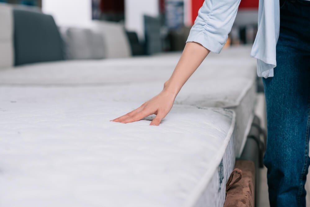 Žena dotykom skúša biely matrac na posteli