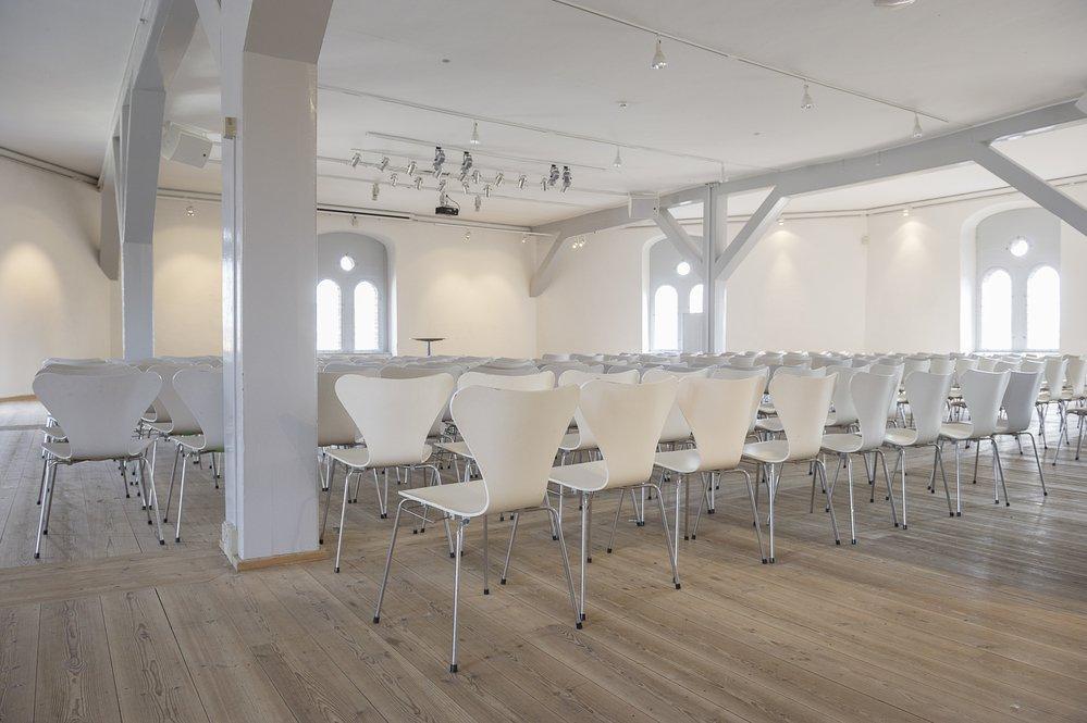 Biele plastové zasadacie stoličky vo veľkej hale
