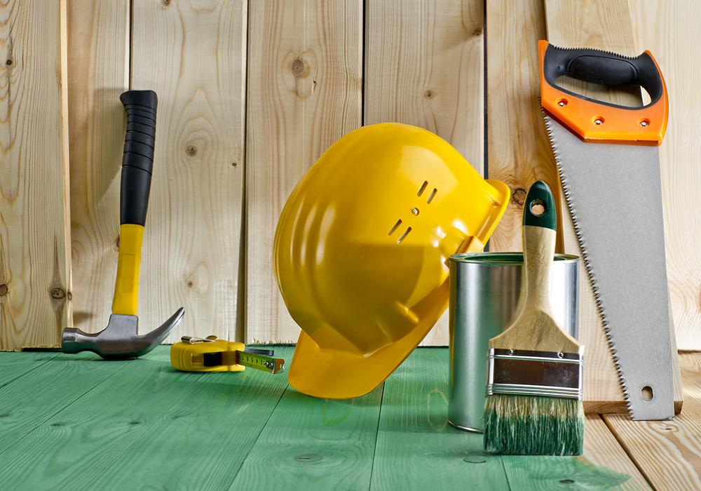 Helma, píla, kladivo a iné náradie na zelenej podlahe