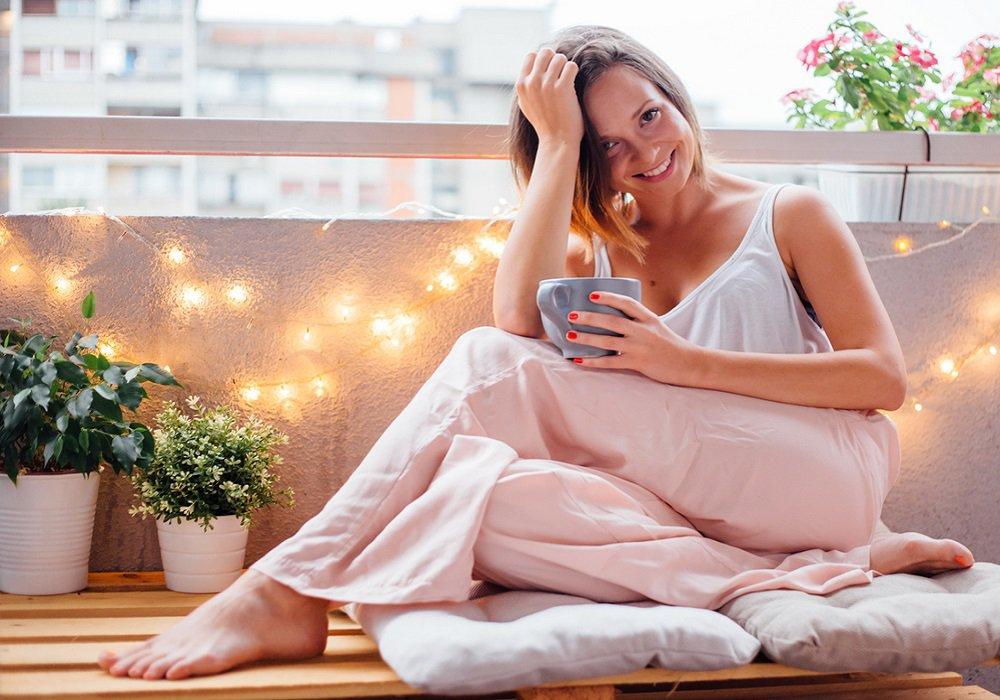 Žena sediaca na balkóne so svetielkami