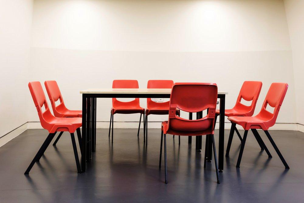 Oranžové plastové konferenčné stoličky za stolom