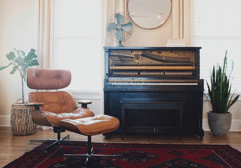 Moderné kreslo pri starodávnom klavíri