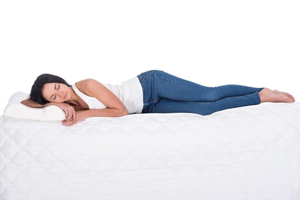 Žena spí na matraci na boku
