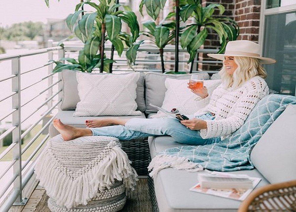 Žena s klobúkom a nápojom na balkóne