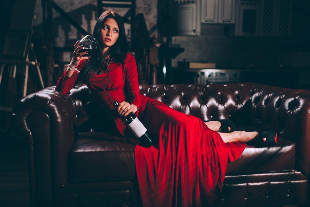 Žena v červených šatách na pohovke chesterfield
