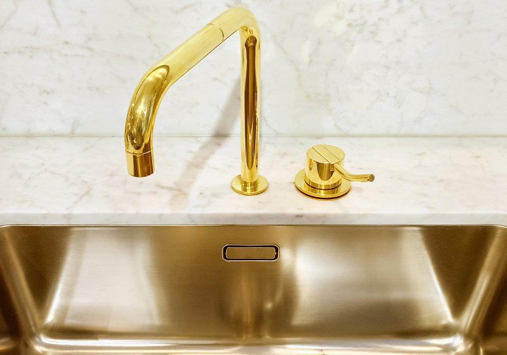 Zlaté umývadlo a kohútik v modernej kuchyni
