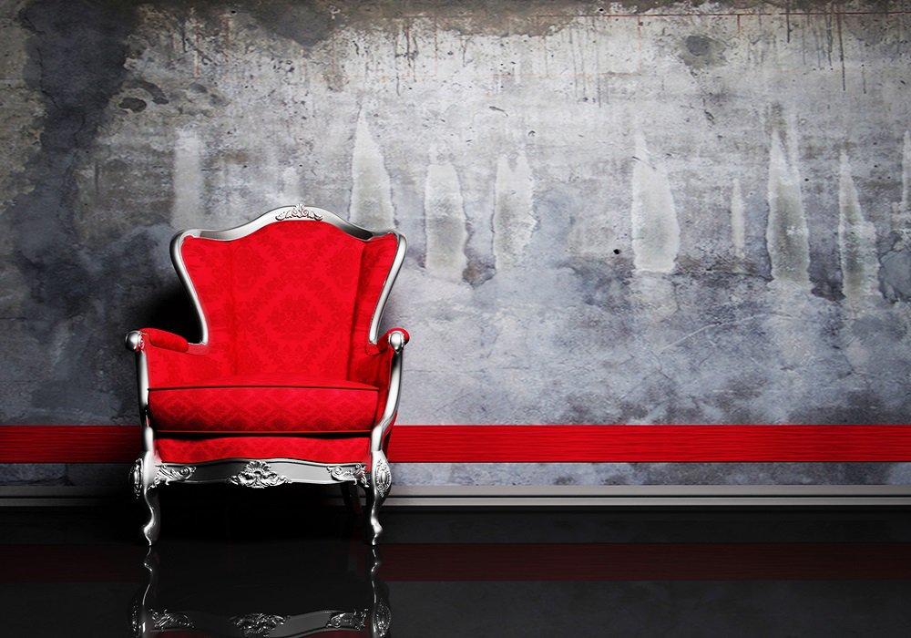 Červené kreslo a červený pás na sivej stene